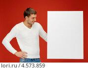 Привлекательный молодой человек с белым билбордом. Стоковое фото, фотограф Syda Productions / Фотобанк Лори