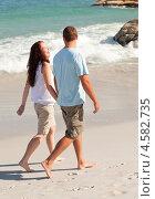 Молодая семейная пара идет по пустынному пляжу вдоль моря. Стоковое фото, агентство Wavebreak Media / Фотобанк Лори