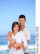 Молодая семейная пара стоит на фоне моря в солнечную погоду. Стоковое фото, агентство Wavebreak Media / Фотобанк Лори