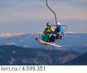 Два лыжника сидят на подъемнике на горнолыжном курорте Шерегеш (2013 год). Редакционное фото, фотограф Алексей Кокоулин / Фотобанк Лори