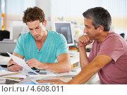 Купить «Два мужчины разговаривают, сидя за столом в офисе», фото № 4608011, снято 22 октября 2012 г. (c) Monkey Business Images / Фотобанк Лори