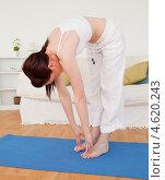Брюнетка выполняет наклоны вперед, делая дома гимнастику. Стоковое фото, агентство Wavebreak Media / Фотобанк Лори