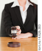 Купить «Девушка стучит судейским молотком, сидя за столом», фото № 4626383, снято 25 мая 2011 г. (c) Wavebreak Media / Фотобанк Лори