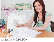 Купить «Улыбающаяся молодая женщина дома шьет на швейной машинке», фото № 4626967, снято 13 мая 2011 г. (c) Wavebreak Media / Фотобанк Лори