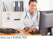 Купить «Женщина-доктор смотрит в компьютер, держа в руках очки», фото № 4654703, снято 11 июля 2011 г. (c) Wavebreak Media / Фотобанк Лори