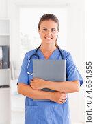 Купить «Симпатичная девушка в синем хирургическом костюме держит серую папку в руках», фото № 4654955, снято 11 июля 2011 г. (c) Wavebreak Media / Фотобанк Лори
