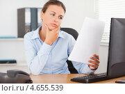 Задумчивая деловая женщина читает документы за столом в офисе. Стоковое фото, агентство Wavebreak Media / Фотобанк Лори