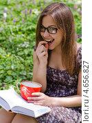 Милая девушка в очках читает книгу и ест клубнику. Стоковое фото, фотограф Mykhaylo Mykulyak / Фотобанк Лори