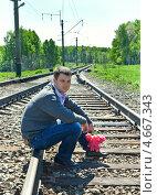 Купить «Мужчина с цветами сидит на рельсах», фото № 4667343, снято 21 января 2019 г. (c) Элина Гаревская / Фотобанк Лори