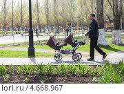 Купить «Мужчина с детской коляской для двойни гуляет в парке», фото № 4668967, снято 24 июня 2018 г. (c) FotograFF / Фотобанк Лори