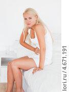 Купить «Симпатичная блондинка смотрит в камеру, приложив руки к животу во время приступа», фото № 4671191, снято 14 июля 2011 г. (c) Wavebreak Media / Фотобанк Лори