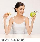 Купить «Привлекательная стройная женщина перед выбором между гамбургером и здоровой пищей», фото № 4678459, снято 6 января 2013 г. (c) Syda Productions / Фотобанк Лори