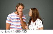 Купить «Woman telling her friend a massive secret on grey background», видеоролик № 4686455, снято 17 июля 2019 г. (c) Wavebreak Media / Фотобанк Лори