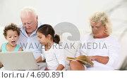 Купить «Family using a laptop and reading book», видеоролик № 4690891, снято 22 июля 2019 г. (c) Wavebreak Media / Фотобанк Лори