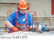 Купить «Рабочий в оранжевой каске и наушниках на объекте», фото № 4691875, снято 24 мая 2013 г. (c) Дмитрий Калиновский / Фотобанк Лори