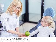Купить «Веселая девочка на приеме у стоматолога. Врач протягивает пациентке зеленое яблоко», фото № 4698859, снято 21 марта 2013 г. (c) Raev Denis / Фотобанк Лори