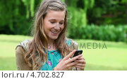 Купить «Smiling young woman typing on her cellphone», видеоролик № 4702827, снято 15 октября 2019 г. (c) Wavebreak Media / Фотобанк Лори