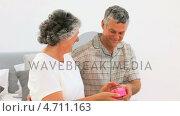 Купить «Mature man offering a present to his wife», видеоролик № 4711163, снято 17 июля 2019 г. (c) Wavebreak Media / Фотобанк Лори