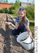 Купить «Девочка-подросток сажает картофель», эксклюзивное фото № 4711755, снято 31 мая 2013 г. (c) Ольга Линевская / Фотобанк Лори