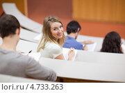 Купить «Девушка обернулась, сидя на лекции в институтской аудитории», фото № 4733263, снято 2 сентября 2011 г. (c) Wavebreak Media / Фотобанк Лори