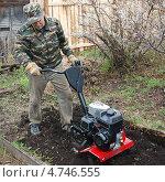 Дачник мужчина рыхлит почву мотокультиватором. Стоковое фото, фотограф Елена Бачурина / Фотобанк Лори