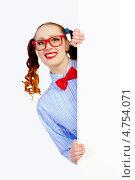 Купить «Рыжая девушка в смешных очках выглядывает из-за баннера», фото № 4754071, снято 15 марта 2013 г. (c) Sergey Nivens / Фотобанк Лори