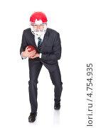 Купить «Бизнесмен в костюме и шлеме игрока американского футбола идет на прорыв с мячом», фото № 4754935, снято 18 ноября 2012 г. (c) Андрей Попов / Фотобанк Лори
