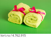 Купить «Два свернутых полотенца с бантом на зеленом фоне», фото № 4762915, снято 11 мая 2013 г. (c) Валерия Потапова / Фотобанк Лори