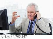 Купить «Сконцентрированный недовольный пожилой мужчина говорит по телефону», фото № 4763247, снято 10 ноября 2011 г. (c) Wavebreak Media / Фотобанк Лори