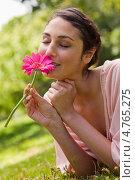Купить «Красивая девушка улыбается, лежа на траве и вдыхая аромат цветка в руках», фото № 4765275, снято 16 ноября 2011 г. (c) Wavebreak Media / Фотобанк Лори