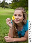 Купить «Красивая длинноволосая девушка вдыхает аромат цветка в руке, лежа на траве», фото № 4765567, снято 14 ноября 2011 г. (c) Wavebreak Media / Фотобанк Лори