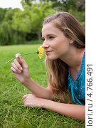 Купить «Красивая девушка лежит на траве в парке и держит в руке цветок, вдыхая его аромат», фото № 4766491, снято 14 ноября 2011 г. (c) Wavebreak Media / Фотобанк Лори