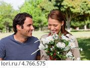 Купить «Красивая молодая женщина вдыхает аромат цветов, а мужчина смотрит на нее», фото № 4766575, снято 16 ноября 2011 г. (c) Wavebreak Media / Фотобанк Лори