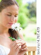 Купить «Симпатичная молодая женщина держит в руках цветы и вдыхает их аромат закрыв глаза», фото № 4767479, снято 17 ноября 2011 г. (c) Wavebreak Media / Фотобанк Лори