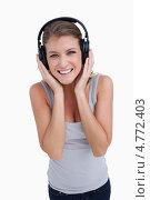 Купить «Улыбающаяся девушка приложила руки к наушникам слушая музыку», фото № 4772403, снято 10 ноября 2011 г. (c) Wavebreak Media / Фотобанк Лори