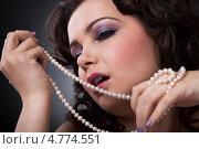 Купить «Красивая шатенка держит длинное жемчужное ожерелье», фото № 4774551, снято 4 января 2013 г. (c) Андрей Попов / Фотобанк Лори