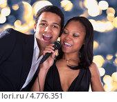 Купить «Красивая темнокожая пара поет в микрофон на фоне ярких огней», фото № 4776351, снято 9 марта 2013 г. (c) Андрей Попов / Фотобанк Лори