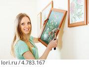Радостная девушка вешает картину. Стоковое фото, фотограф Яков Филимонов / Фотобанк Лори