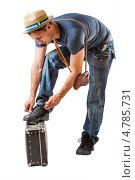 Купить «Мужчина-путешественник завязывает шнурки, поставив ногу на старый чемодан», фото № 4785731, снято 16 июня 2013 г. (c) katalinks / Фотобанк Лори
