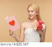 Счастливая девушка с цветами и любовным посланием в открытке. Стоковое фото, фотограф Syda Productions / Фотобанк Лори