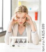 Купить «Усталая женщина в офисе наблюдает за песочными часами», фото № 4825699, снято 17 июня 2012 г. (c) Syda Productions / Фотобанк Лори