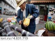 Купить «Китайский торговец фруктами чистит тесаком ананас на уличном рынке в Шанхае», эксклюзивное фото № 4831719, снято 10 мая 2013 г. (c) Николай Винокуров / Фотобанк Лори