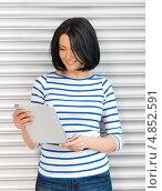 Купить «Молодая брюнетка с длинным каре с тонким планшетным компьютером», фото № 4852591, снято 7 апреля 2012 г. (c) Syda Productions / Фотобанк Лори