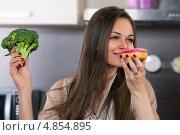 Молодая женщина выбирает что кушать овощи или пончик. Стоковое фото, фотограф Okssi / Фотобанк Лори