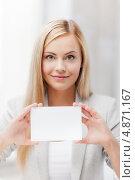 Купить «Привлекательная блондинка с белой карточкой в руках», фото № 4871167, снято 30 марта 2013 г. (c) Syda Productions / Фотобанк Лори