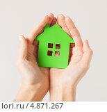 Купить «Девушка держит в руках зеленый картонный домик», фото № 4871267, снято 28 марта 2013 г. (c) Syda Productions / Фотобанк Лори