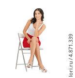 Купить «Красивая брюнетка в красной юбке сидит на стуле на белом фоне», фото № 4871339, снято 12 апреля 2012 г. (c) Syda Productions / Фотобанк Лори
