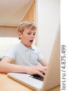 Изображение удивленного мальчика, пользующегося ноутбуком. Стоковое фото, агентство Wavebreak Media / Фотобанк Лори