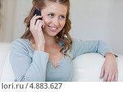 Купить «Женщина сидит на диване слушая звонящего», фото № 4883627, снято 1 ноября 2011 г. (c) Wavebreak Media / Фотобанк Лори