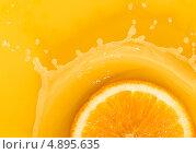 Долька апельсина падает в апельсиновый сок. Стоковое фото, фотограф Владислав Серкин / Фотобанк Лори
